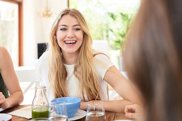 Laughing blonde girl at kitchen table.