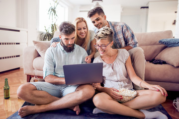 Group of friends sitting on sofa with laptop