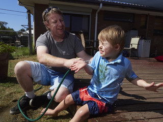 Preschool Child Being Washed Down by Dad in Backyard