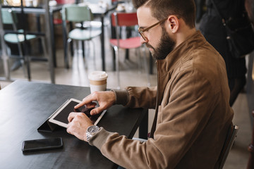 Man working with tablet in cafe