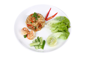 Fried rice with shrimp topped sliced red hot chili pepper,sliced cucumber ,halved green lemon and garlic on white plate.