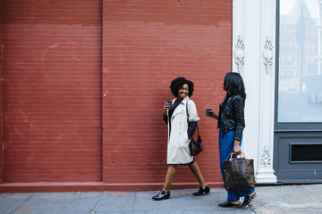 two women walking along a city sidewalk