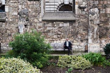 Businessman on bench in garden.