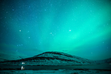 Northern lights over the snowy mountains and stars sky at winter