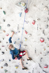 Senior man rock climbing indoors on an artificial wall
