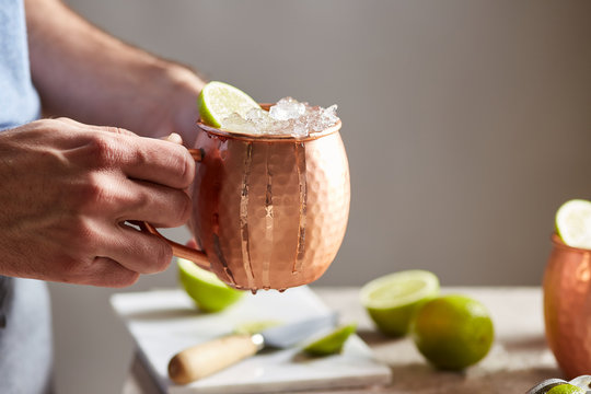 Bartender with fresh Moscow mule cocktail.