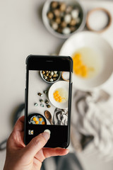 Person photographing quail eggs with mobile phone