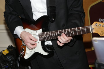 Musician playing white black brown electric guitar during an event