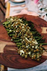 Asparagus sitting on a wooden serving platter