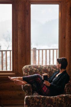 Woman With Plaid Tights At Ski Chalet Enjoying Morning Coffee