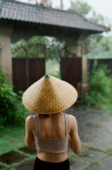 Back view of a woman wearing conical hat during wet season
