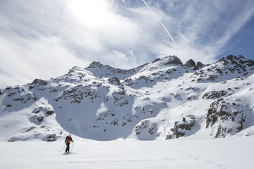 Mountaineer crossing a snowy lake at the Pyrenees