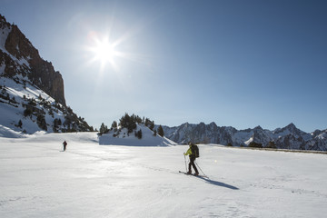 Mountaineers crossing a snowy lake in a sunny day, Pyrenees