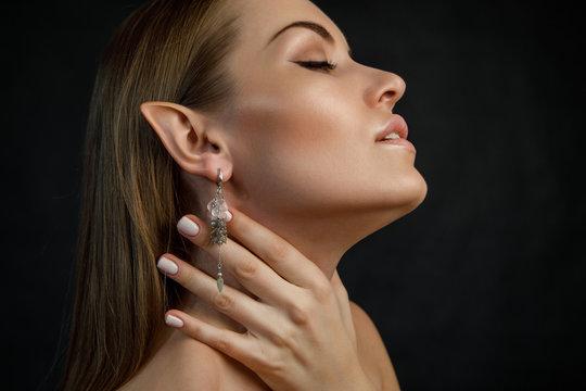красивая женщина с эльфийским ухом и серьгами чувственно держит себя за шею