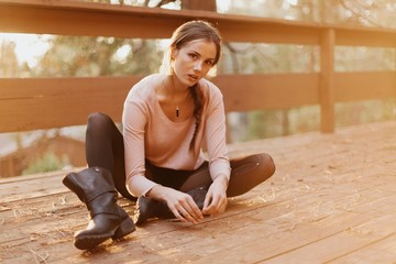 Haunting Young Woman Sitting on a Deck