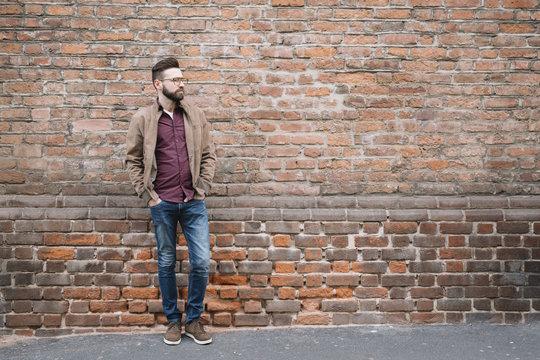 Stylish man at brick wall