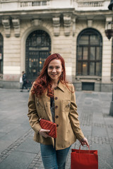 Redhead Woman Standing in the Street Holding her Wallet and Shopping Bag
