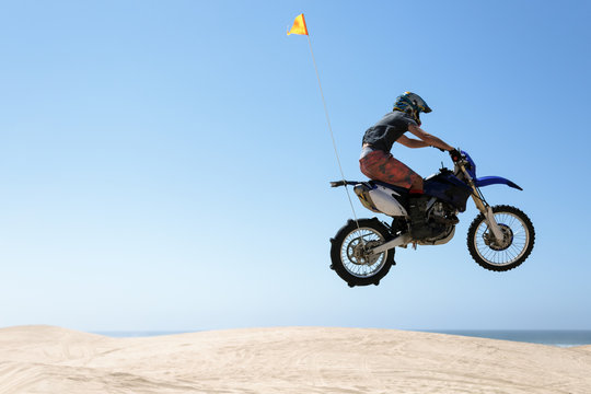 Teenager jumping sand dunes on a motorcycle