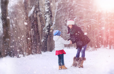 A winter fairy tale, a young mother and her daughter ride a sled