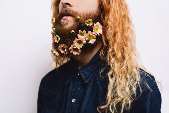 Portrait of a young man holding flowers in his beard.