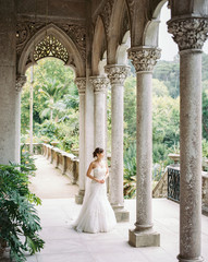 Bride stands near columns