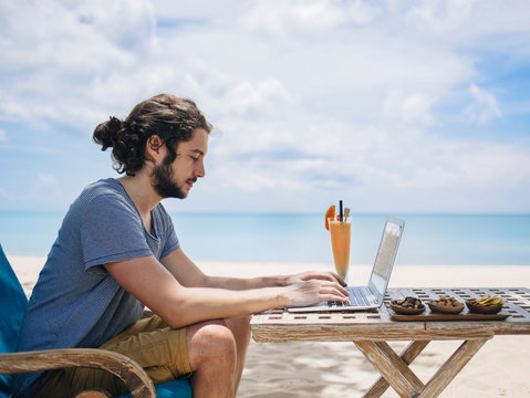 Man using laptop and phone on beach