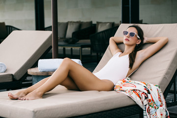 Beautiful Slim Sensual Caucasian Woman in Pink Swimsuit Relaxing on Sunbed