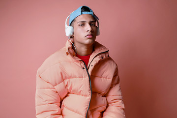 Portrait of a young man listening to music wearing a pink coat