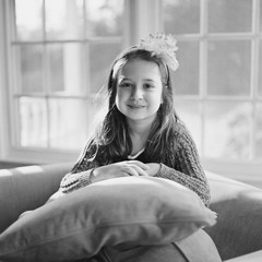 Cute young girl with a bow in her hair sitting amongst pillows looking at the camera