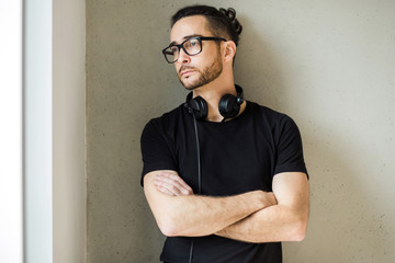 Handsome man in his early 40 in a black t-shirt wearing glasses and headphones around his neck