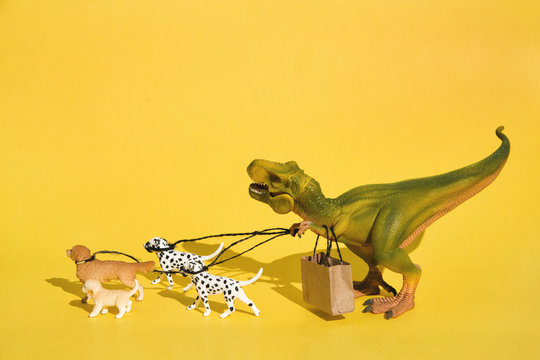 Plastic T-Rex with dogs on walk
