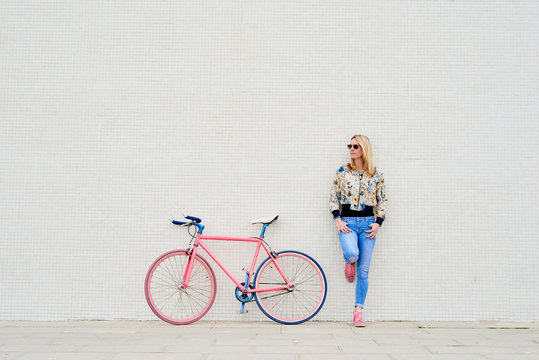 Stylish woman with fixie over white wall.