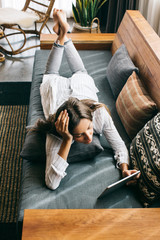 Young Pretty Woman Lying on Sofa and Looking at Digital Tablet Computer