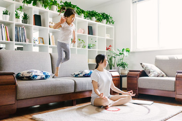 Adorable little girl doing yoga with her mother