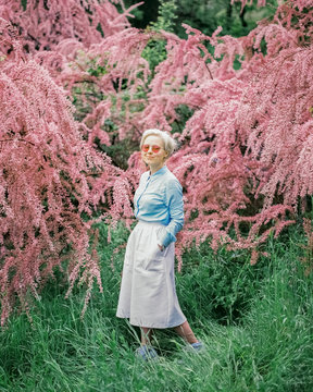 Portrait of female standing near pink trees