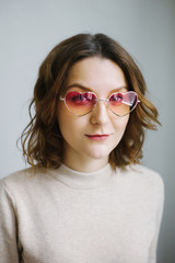 Female wearing pink heart shaped sunglasses