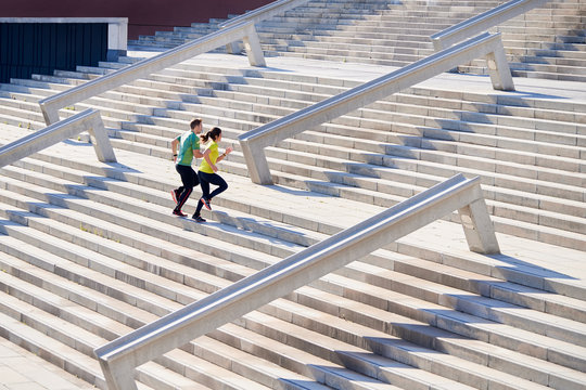 Fast running couple going up on stairs.