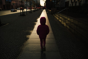 Anonymous girl on straight path in golden light.