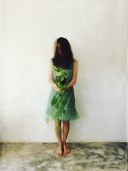 Movement shot of unrecognisable female wearing  green dress, holding Devil's Ivy plant