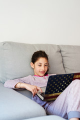 LIttle girl using her laptop at home