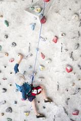 Senior man rock climbing indoors on an artificial wall
