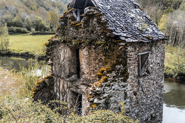 front of old ruined house on the river Aveyron Belcastel France