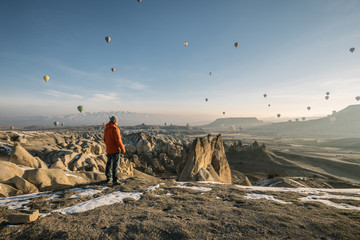 young male traveller overlooking landscape of cappadocia with dozens of colorful hot air balloons at sunrise, turkey
