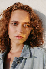 Portrait of young curly woman with flares on her face