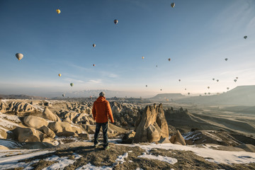 young male adventurer overlooking landscape of cappadocia with dozens of colorful hot air balloons at sunrise, turkey