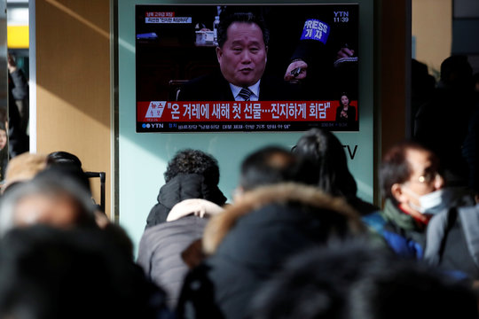 People watch a TV broadcasting a news report on a high-level talks between the two Koreas at the truce village of Panmunjom, in Seoul