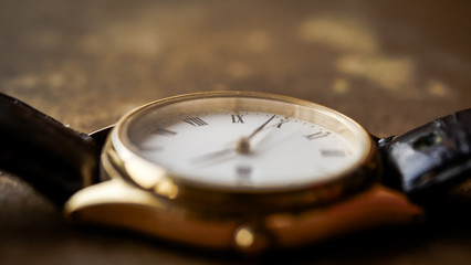 Close up front view of a modern wrist watch on the table. Soft focus