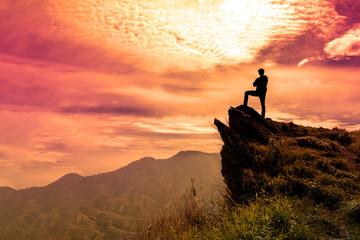 Zelfklevend Fotobehang Diepbruine The man stands on a cliff top and orange