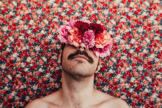man wint flowers covering his eyes behind a foral bakground