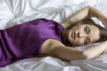 beautiful young woman in purple dress lying on bed